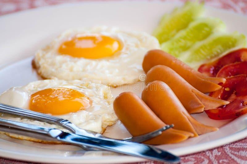 Desayune con los huevos fritos, las salchichas, el cereal, las tostadas y el café foto de archivo