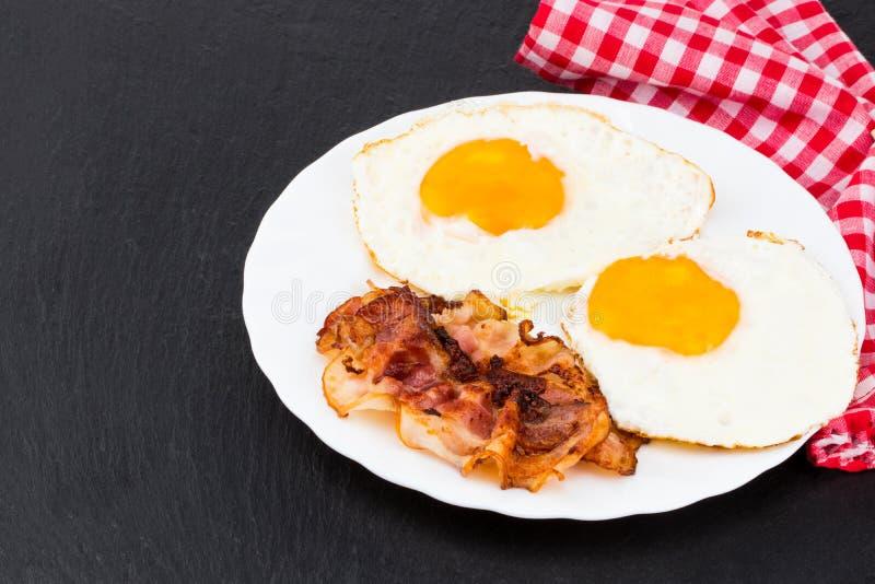 Desayune con los huevos fritos y el tocino en fondo de piedra oscuro fotografía de archivo libre de regalías