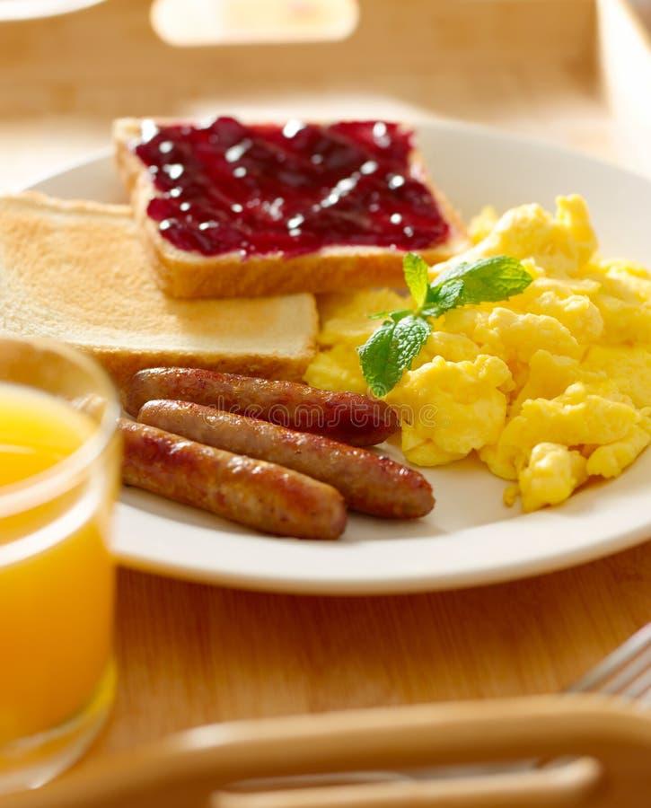 Desayune con los huevos revueltos, los vínculos de la salchicha y tostada. imágenes de archivo libres de regalías