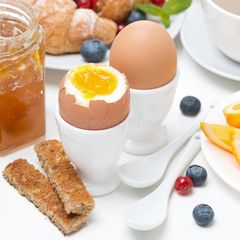 Desayune con los huevos, tostadas, cruasanes, bayas frescas imagenes de archivo