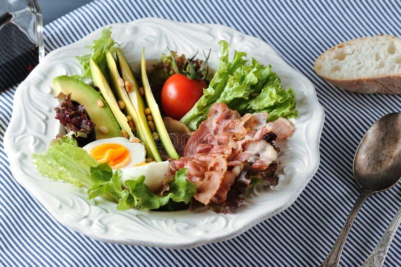 Desayune con tocino, el aguacate, el huevo y la ensalada en una servilleta fotos de archivo libres de regalías