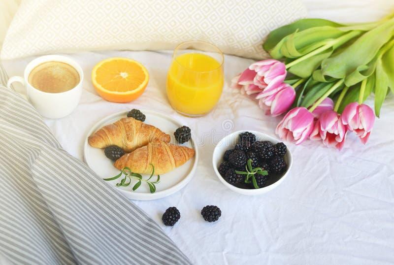 Desayune en la cama, cruasán, taza de café, bayas, zumo de naranja, imágenes de archivo libres de regalías
