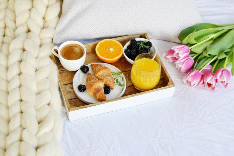 Desayune en la cama, cruasán, taza de café, bayas, zumo de naranja, tulipanes rosados imágenes de archivo libres de regalías