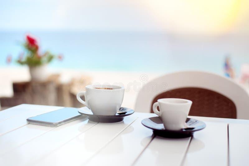 Desayune para dos en un café en la playa con dos tazas de café imagen de archivo libre de regalías