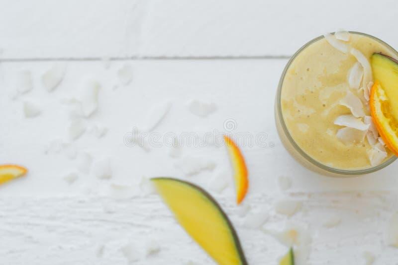 Desayuno útil: smoothies del mango, del plátano y de la naranja en un whi fotos de archivo
