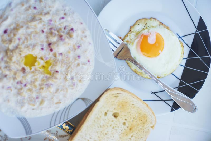 Desayuno acogedor de la familia por el mar: huevos fritos, café sólo clásico, cereal, jugo, tocino en una placa y con las verdura foto de archivo libre de regalías