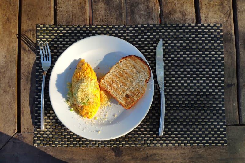 Desayuno al aire libre Una tortilla en una placa blanca Bifurcaci?n y cuchillo en la tabla de madera fotografía de archivo