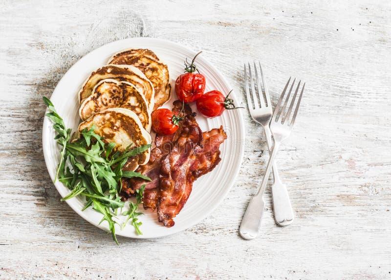 Desayuno americano tradicional - el tocino curruscante, crepes con el jarabe de arce, asó los tomates, arugula En un fondo ligero imagenes de archivo