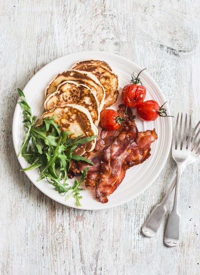 Desayuno americano tradicional - el tocino curruscante, crepes con el jarabe de arce, asó los tomates, arugula En un fondo ligero fotografía de archivo libre de regalías