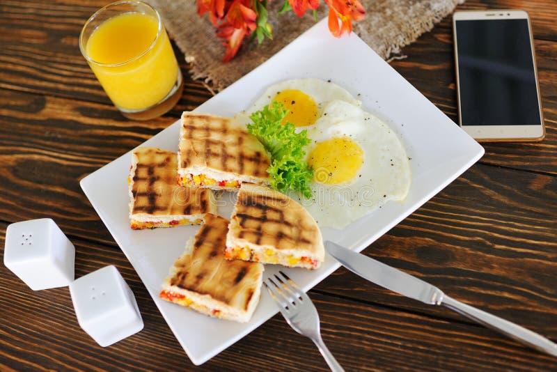 Desayuno - bocadillos con maíz en un fondo de madera en un fondo de huevos revueltos, arpillera, smartphone y fotografía de archivo