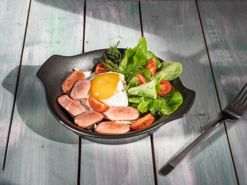 Desayuno caluroso de huevos revueltos con las salchichas, los tomates y la lechuga de hoja Servicio en una bandeja rústica de mad fotos de archivo