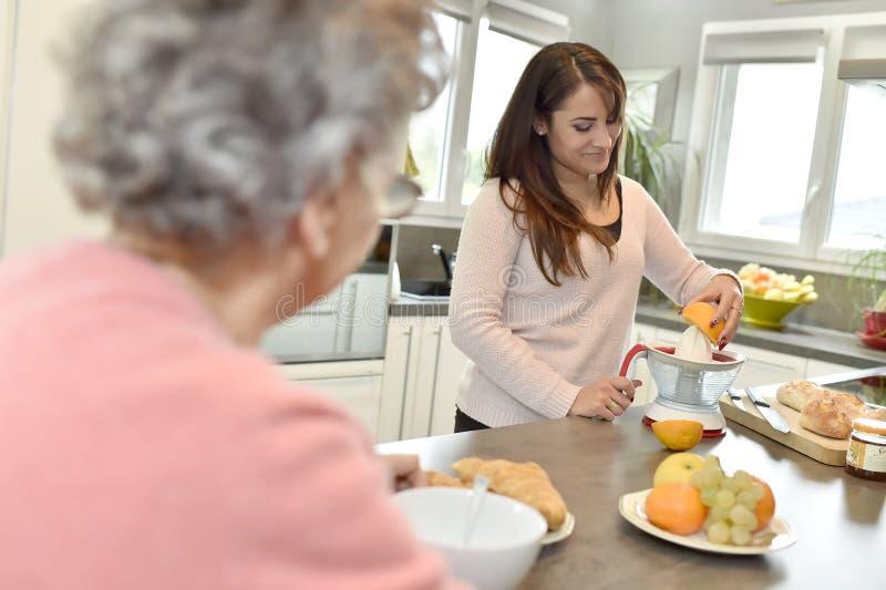 Desayuno casero de la porción del cuidador a una mujer mayor fotografía de archivo libre de regalías