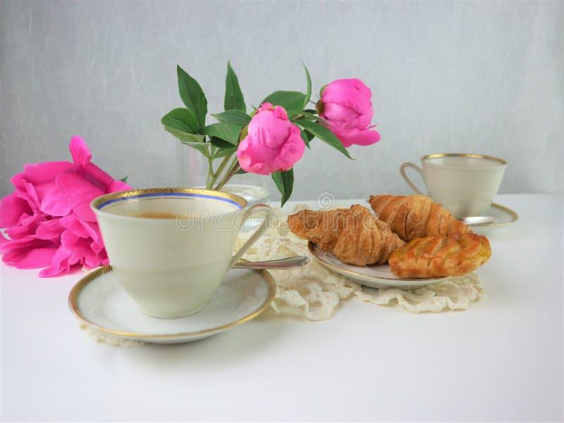 Desayuno con dos tazas del caf? y de los cruasanes, ramo de flores rosadas imagenes de archivo