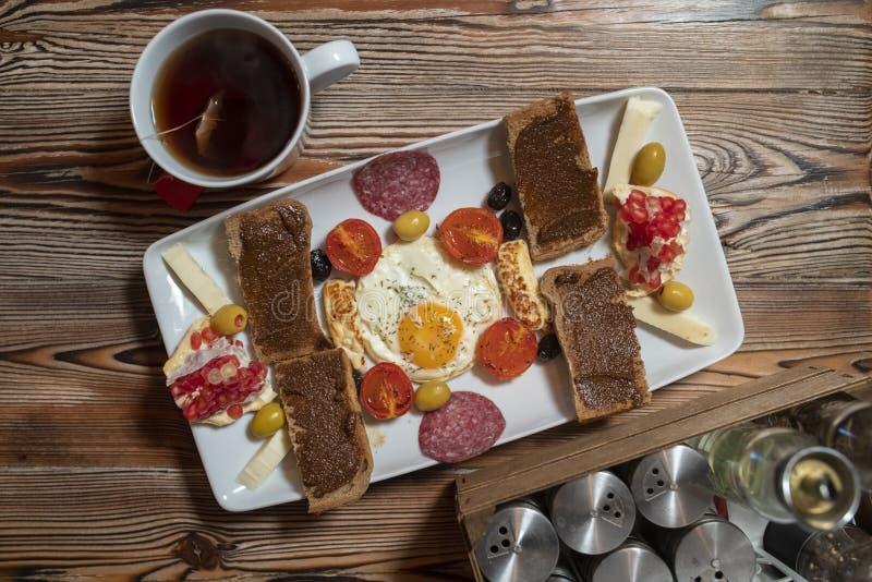 Desayuno con el huevo frito, el pan de centeno, la granada, la goma de la algarroba, quesos, las aceitunas, el salami seco, los t imágenes de archivo libres de regalías