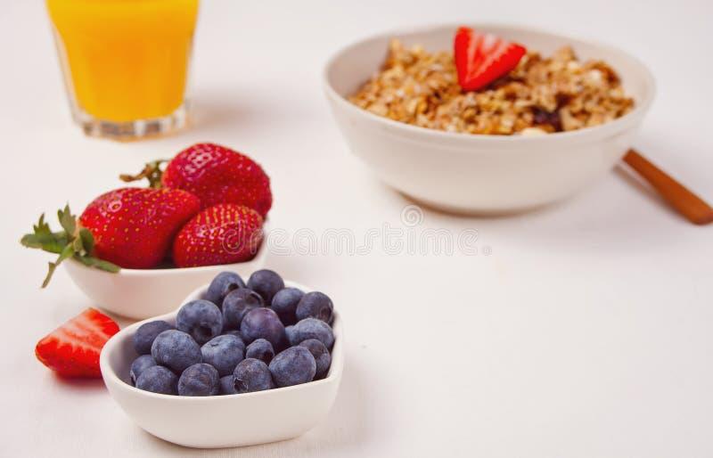 Desayuno con el muesli, bayas en el fondo blanco fotos de archivo