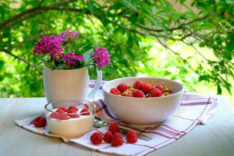 Desayuno con las frambuesas, el yogur y el granola fotografía de archivo libre de regalías