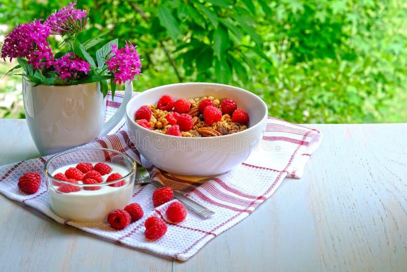 Desayuno con las frambuesas, el yogur y el muesli imágenes de archivo libres de regalías
