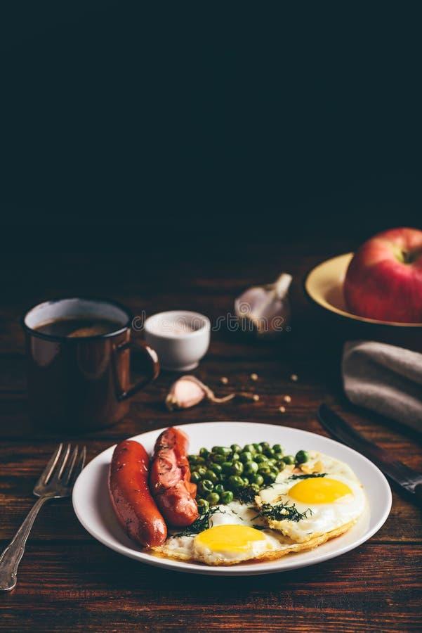 Desayuno con los huevos fritos, las salchichas y los guisantes verdes fotografía de archivo