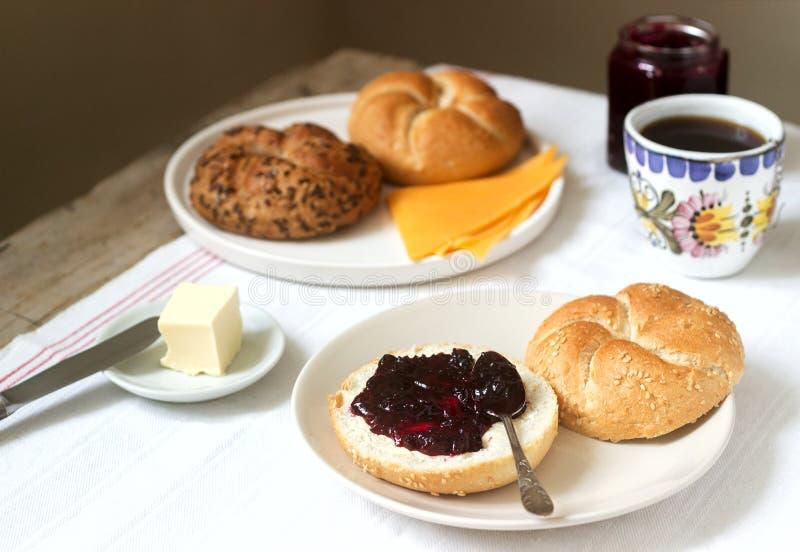 Desayuno con los rollos de Kaiser, atasco de la pasa, mantequilla y queso y té imagen de archivo libre de regalías