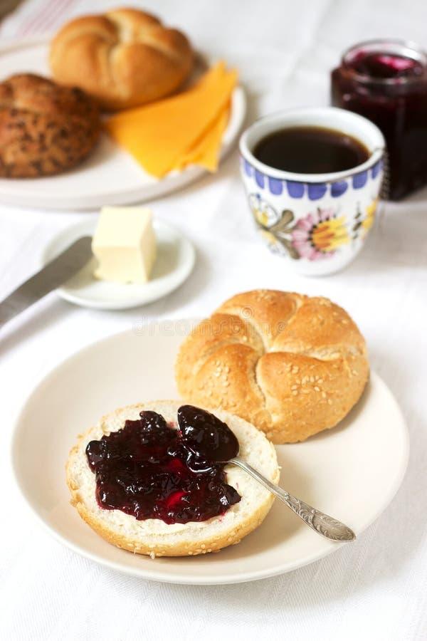 Desayuno con los rollos de Kaiser, atasco de la pasa, mantequilla y queso y té fotografía de archivo