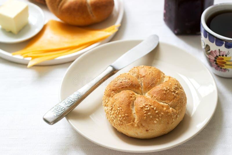 Desayuno con los rollos de Kaiser, atasco de la pasa, mantequilla y queso y té foto de archivo libre de regalías