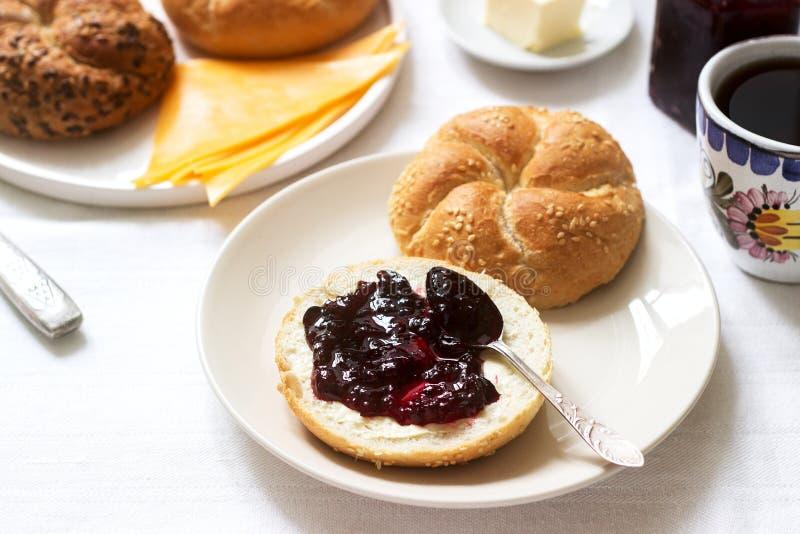 Desayuno con los rollos de Kaiser, atasco de la pasa, mantequilla y queso y té fotos de archivo