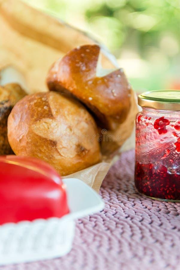 Desayuno con pan hecho en casa del pretzel, atasco rojo y mantequilla foto de archivo