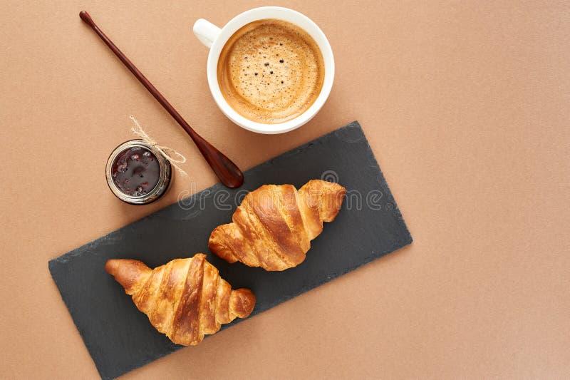 Desayuno de dos cruasanes franceses con el atasco y el café foto de archivo
