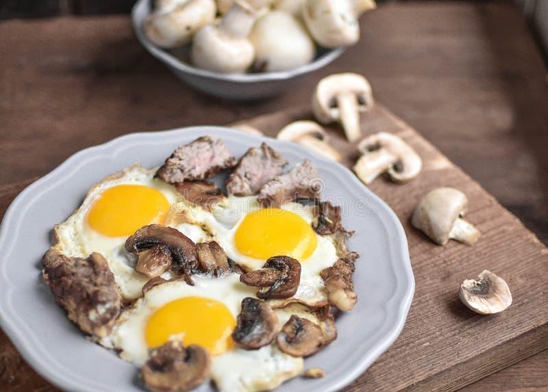 Desayuno de hombre, huevo con champiñones y carne para el desayuno - este es un maravilloso comienzo del día imagen de archivo