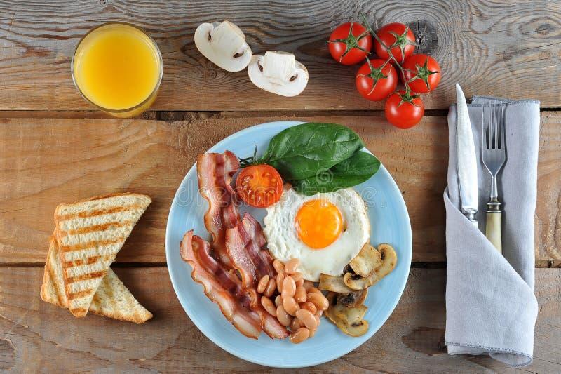 Desayuno de huevos con tocino, habas, setas, los tomates y spi imagen de archivo libre de regalías