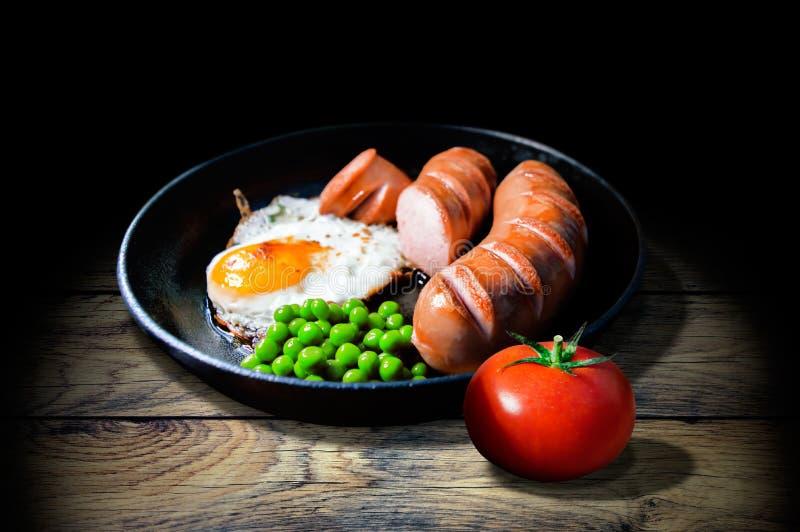 Desayuno de huevos fritos, de salchichas, de guisantes y del tomate fotos de archivo