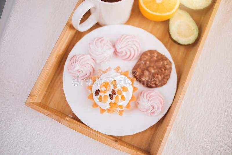 Desayuno de la buena mañana en cama con el té, naranja, aguacate, torta, melcochas, galletas del chocolate en bandeja de madera f foto de archivo libre de regalías