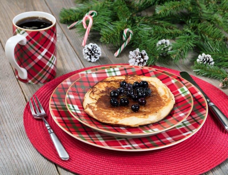 Desayuno de la crepe para el día de la Navidad con las ramas imperecederas en r imagenes de archivo