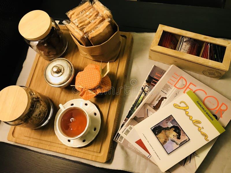 Desayuno de la mañana con té, galletas y revistas foto de archivo
