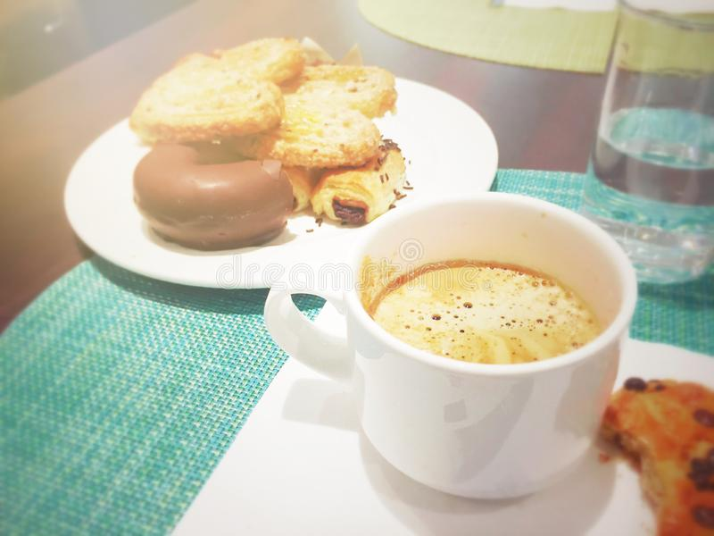 Desayuno de la mañana con una taza de capuchino espumoso con los anillos de espuma de los pasteles y del chocolate fotografía de archivo