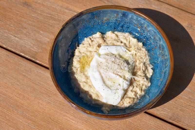 Desayuno de la mañana en una placa azul en la tabla harina de avena sabrosa con el huevo frito, visión superior Desayuno equilibr imagenes de archivo
