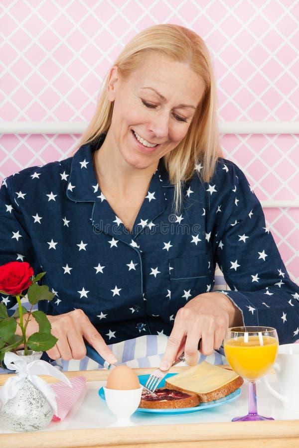Desayuno de la mujer en cama imagen de archivo