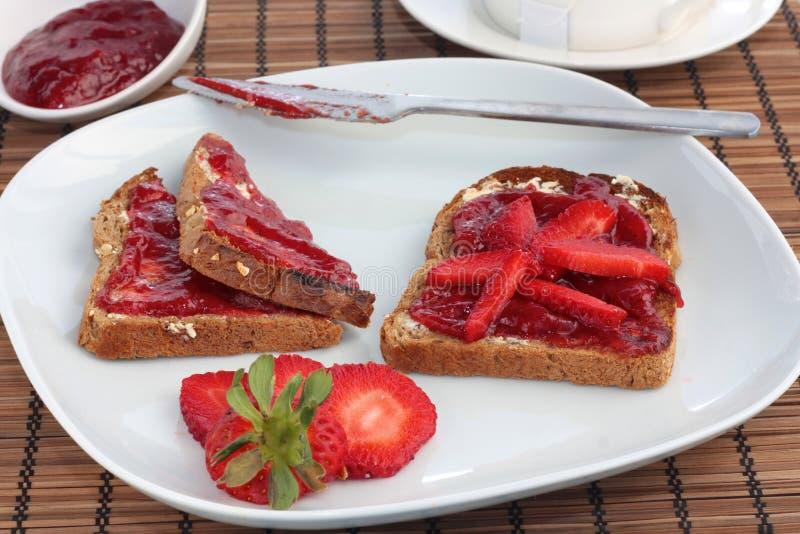 Desayuno de la tostada integral con la jalea de la fresa foto de archivo