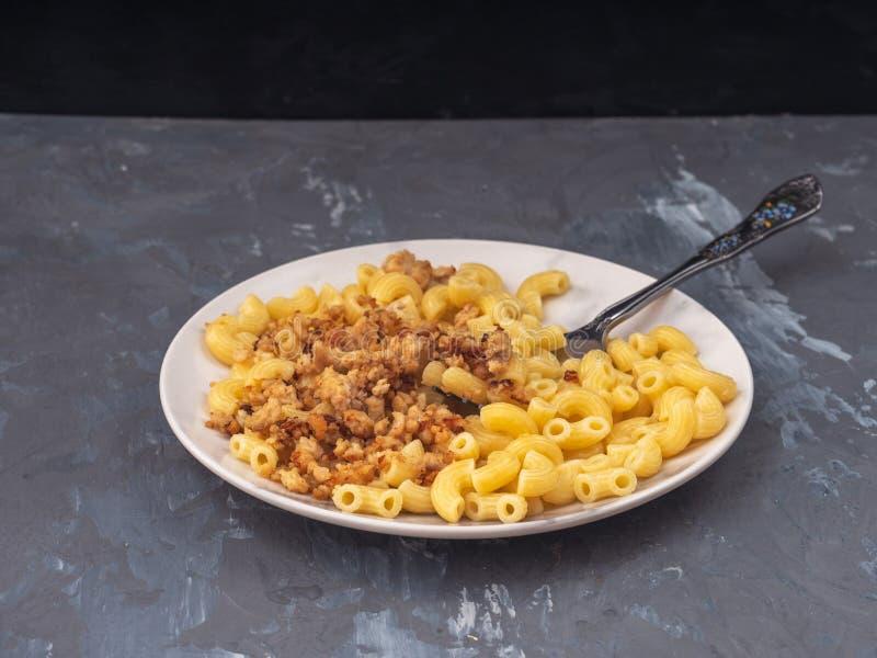 Desayuno de las pastas con el pollo picadito en una placa blanca, bifurcación, primer, vista lateral sobre fondo gris imágenes de archivo libres de regalías