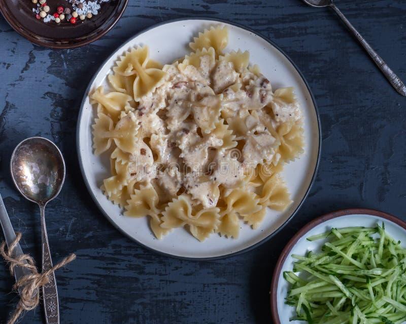 Desayuno de las pastas y de la ensalada fresca del pepino en placas redondas en un fondo gris, las bifurcaciones y las cucharas,  imagenes de archivo