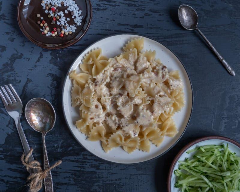 Desayuno de las pastas y de la ensalada fresca del pepino en un fondo gris, bifurcaciones y cucharas, condimentos en un pequeño p imagenes de archivo