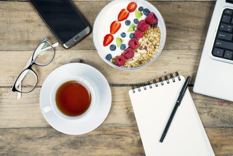 Desayuno del negocio con té y yogur en el escritorio fotografía de archivo libre de regalías