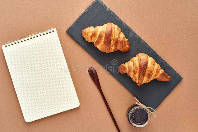 Desayuno del negocio de dos cruasanes franceses con la libreta imágenes de archivo libres de regalías