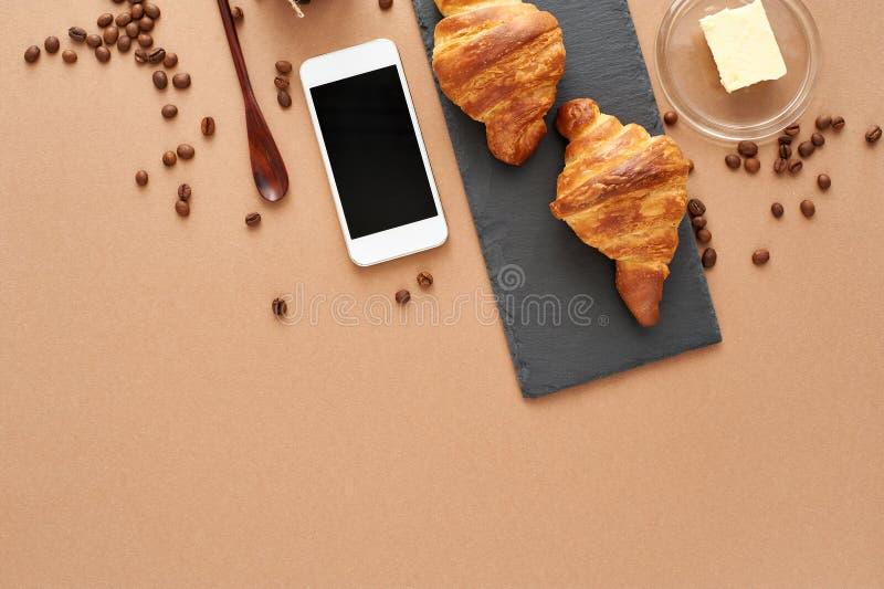Desayuno del negocio de dos cruasanes franceses con smartphone imagen de archivo