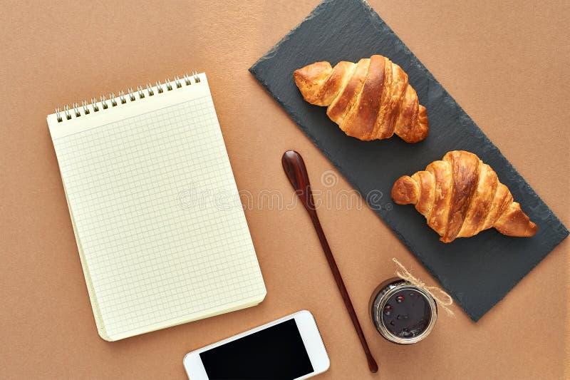 Desayuno del negocio de dos cruasanes franceses con smartphone fotos de archivo libres de regalías