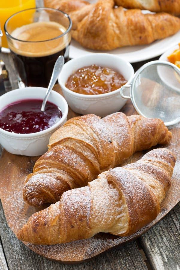 Desayuno delicioso con los cruasanes frescos en la tabla de madera imagen de archivo