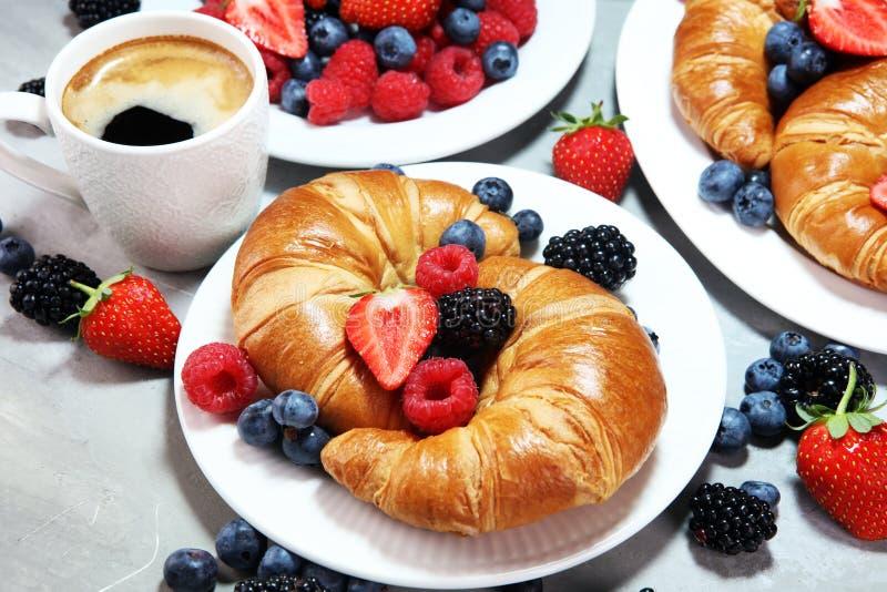 Desayuno delicioso con los cruasanes frescos y las bayas maduras en ol foto de archivo libre de regalías