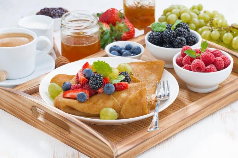 Desayuno delicioso - crespones con las bayas y la miel frescas foto de archivo