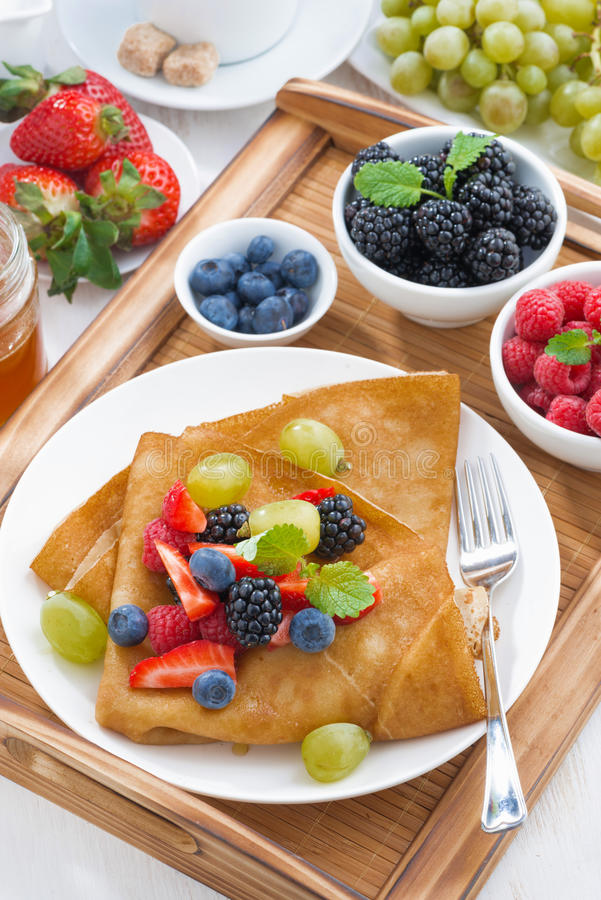 Desayuno delicioso - crespones con las bayas y la miel frescas fotos de archivo