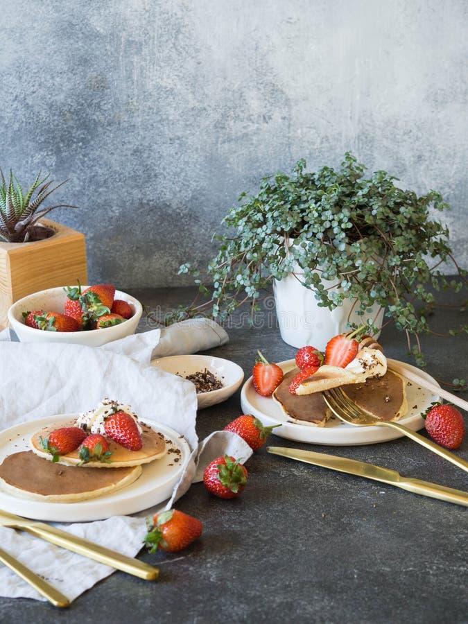 Desayuno delicioso de la forma de vida para dos personas Pila de crepes con la miel y las fresas en las placas blancas imágenes de archivo libres de regalías
